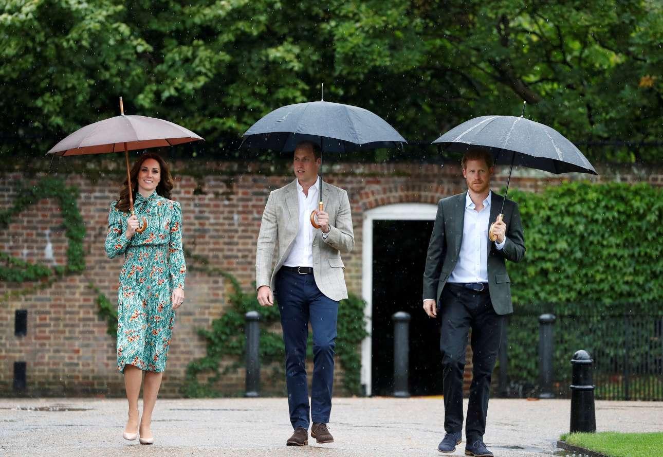 Ο πρίγκιπας Χάρι δεξιά) με τον πριγκιπικό ζεύγος Ουίλιαμ και Κέιτ υπό βροχή στους κήπους της Νταϊάνα. Η Lady K είναι η νέα Lady D στις καρδιές των Βρετανών REUTERS/Kirsty Wigglesworth
