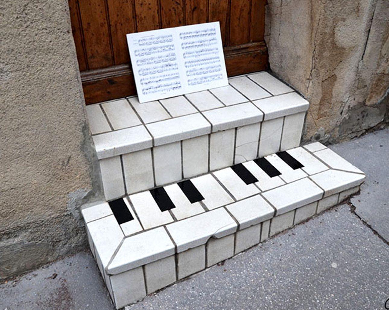 Οι παρτιτούρες μαζί με την ξύλινη πόρτα και τα λευκά σκαλοπάτια, δημιουργούν ένα πολύ αληθοφανές πιάνο