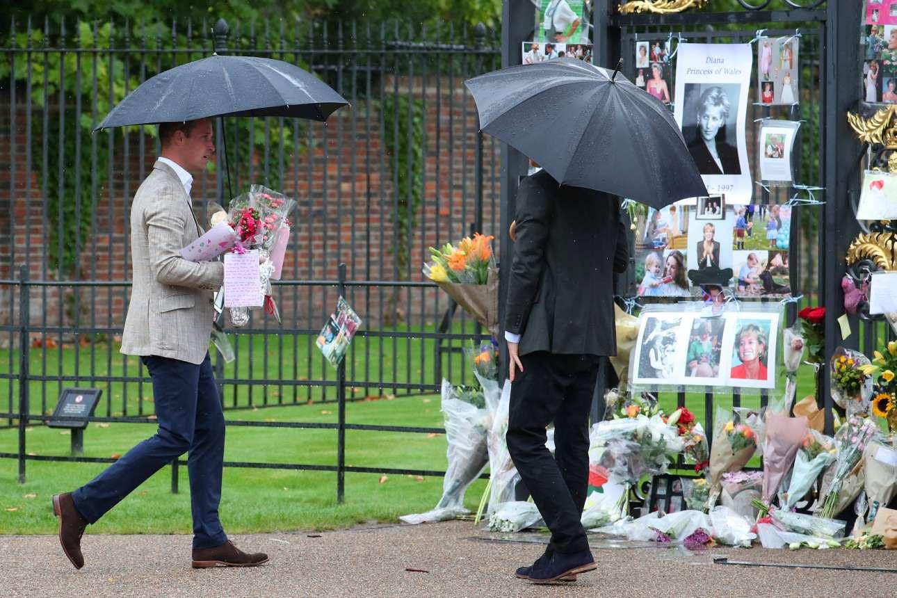 Οι πρίγκιπες Χάρι και Ουίλιαμ αριστερά) ενώ αφήνουν λουλούδια στην είσοδο του παλατιού του Κένσινγκτον REUTERS/Hannah McKay)