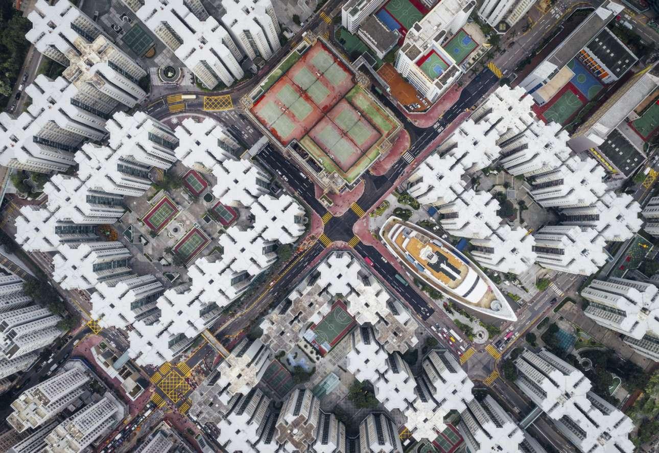 «Περιτειχισμένη Πόλη» - Δεύτερη θέση, κατηγορία Πόλεις. Μέσα στην πυκνοκατοικημένη πόλη του Χονγκ Κονγκ και ανάμεσα στα παράξενα κτίρια με τα ιδιαίτερα μοτίβα κρύβεται μία έκπληξη... ένα εμπορικό κέντρο σε σχήμα καραβιού. Ο φωτογράφος θέλει να δείξει πόσο κλειστοφοβικά είναι να ζεις στο Χονκ Κονγκ από μία διαφορετική γωνία, από ψηλά