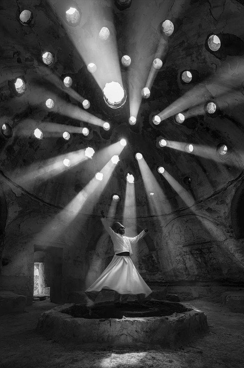 «Λατρεία» - Πρώτη θέση, κατηγορία Ανθρωποι. Ενας περιστρεφόμενος δερβίσης χορεύει εκστασιασμένος σε ένα ιστορικό κτίριο της τουρκικής πόλης Ικόνιο, καθώς οι ακτίνες του ήλιου «τρυπώνουν» από την οροφή. H τελετή των Μεβλεβί συμβολίζει το πνευματικό ταξίδι προς την αγάπη και την αλήθεια