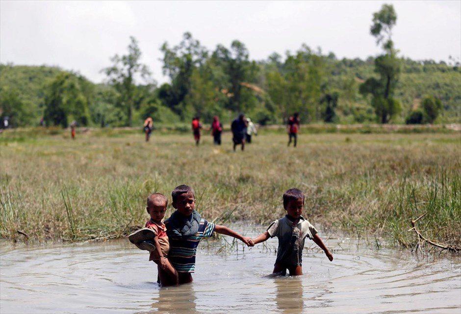Τρίτη, 29 Αυγούστου. Παιδιά της μειονότητας των Ροχίνγκια διασχίζουν τα νερά ενός ποταμού στην προσπάθειά τους να περάσουν στο Μπανγκλαντές. «Τουλάχιστον 3.000 μέλη της μουσουλμανικής μειονότητας των Ροχίνγκια έχουν περάσει τις τρεις τελευταίες ημέρες από τη Μιανμάρ στο Μπανγκλαντές για να γλιτώσουν από τη νέα κλιμάκωση της βίας στην Πολιτεία Ραχίν» ανακοίνωσε ο ΟΗΕ