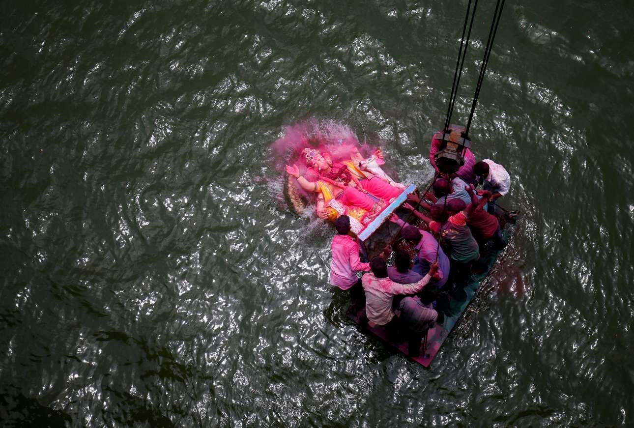 Τρίτη, 5 Σεπτεμβρίου. Πιστοί βυθίζουν είδωλο της ινδουιστικής θεότητας Γκανέσα, που συμβολίζει την ευημερία, στον ποταμό Σαμπαρμάτι κατά την τελευταία ημέρα θρησκευτικού φεστιβάλ στην πόλη Αχμενταμπάντ της Ινδίας