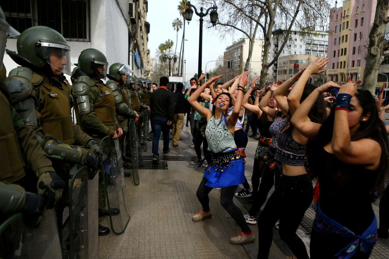Τρίτη, 5 Σεπτεμβρίου. Διαδηλωτές χορεύουν μπροστά στους πάνοπλους άνδρες της αστυνομίας της Χιλής. Οι αλλαγές στο εκπαιδευτικό σύστημα της χώρας έχουν προκαλέσει έντονες αντιδράσεις