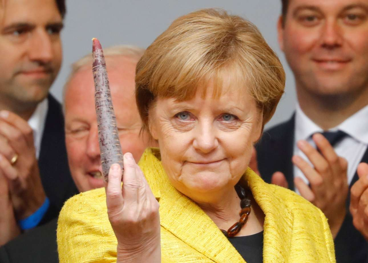 Δευτέρα, 18 Σεπτεμβρίου: Η γερμανίδα καγκελάριος Άνγκελα Μέρκελ κρατά ένα καρότο κατά τη διάρκεια προεκλογικής της συγκέντρωσης στο Φράιμπουργκ