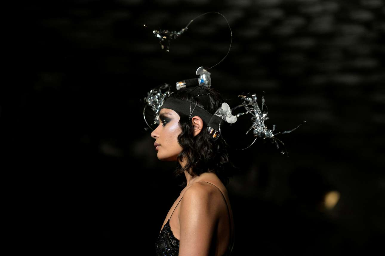 Τα δημιουργήματα του σχεδιαστή Ασίς Γκούπτα έχουν επιρροές από την κουλτούρα της ντίσκο όπως διακρίνεται και στο συγκεκριμένο καπέλο με λαμπτήρες και φωσφορίζοντα διακοσμητικά στοιχεία.