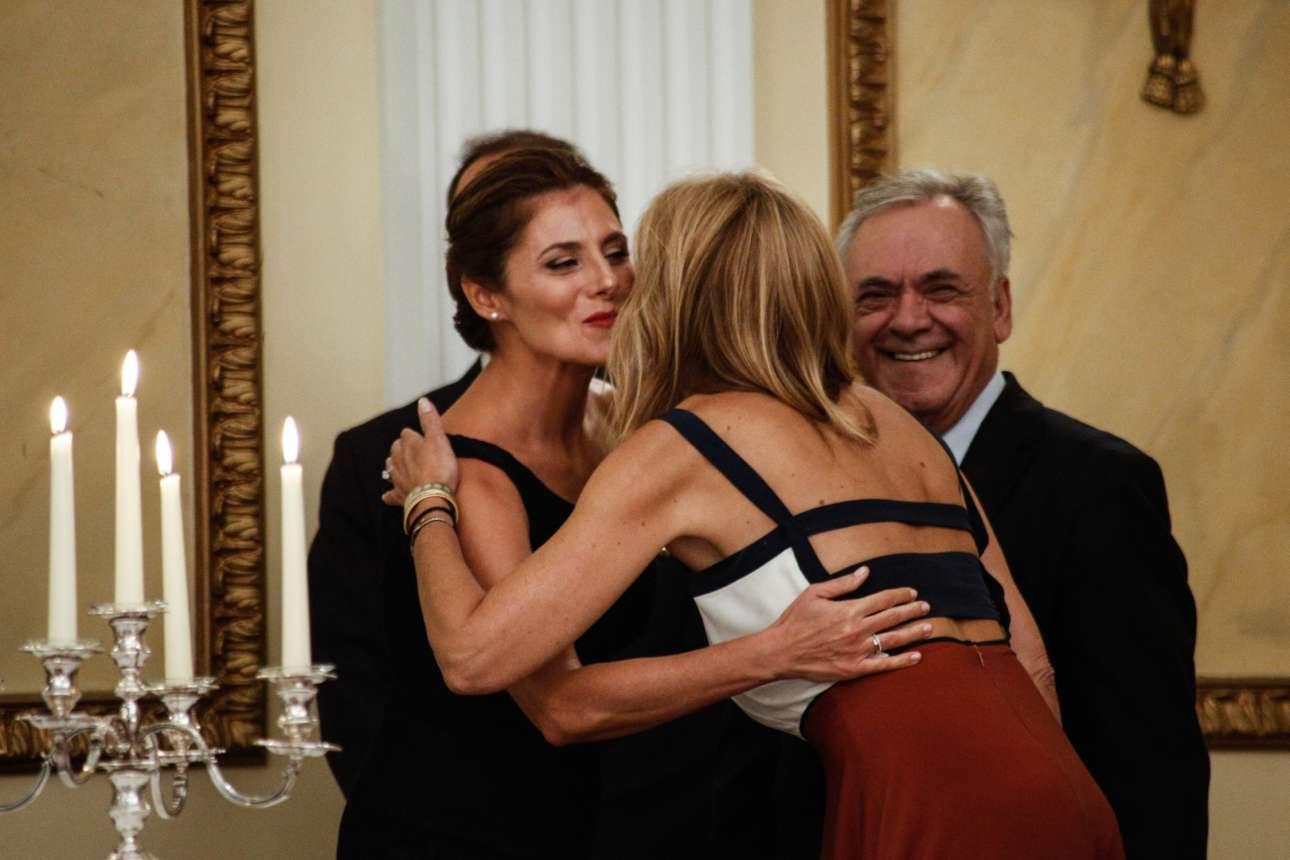 Το φιλί της Μπέτυς Μπαζιάνα στην Μαρέβα Μητσοτάκη. Ο αντιπρόεδρος της κυβερνήσεως Γιάννης Δραγασάκης δεν μπορεί να κρύψει τη χαρά του