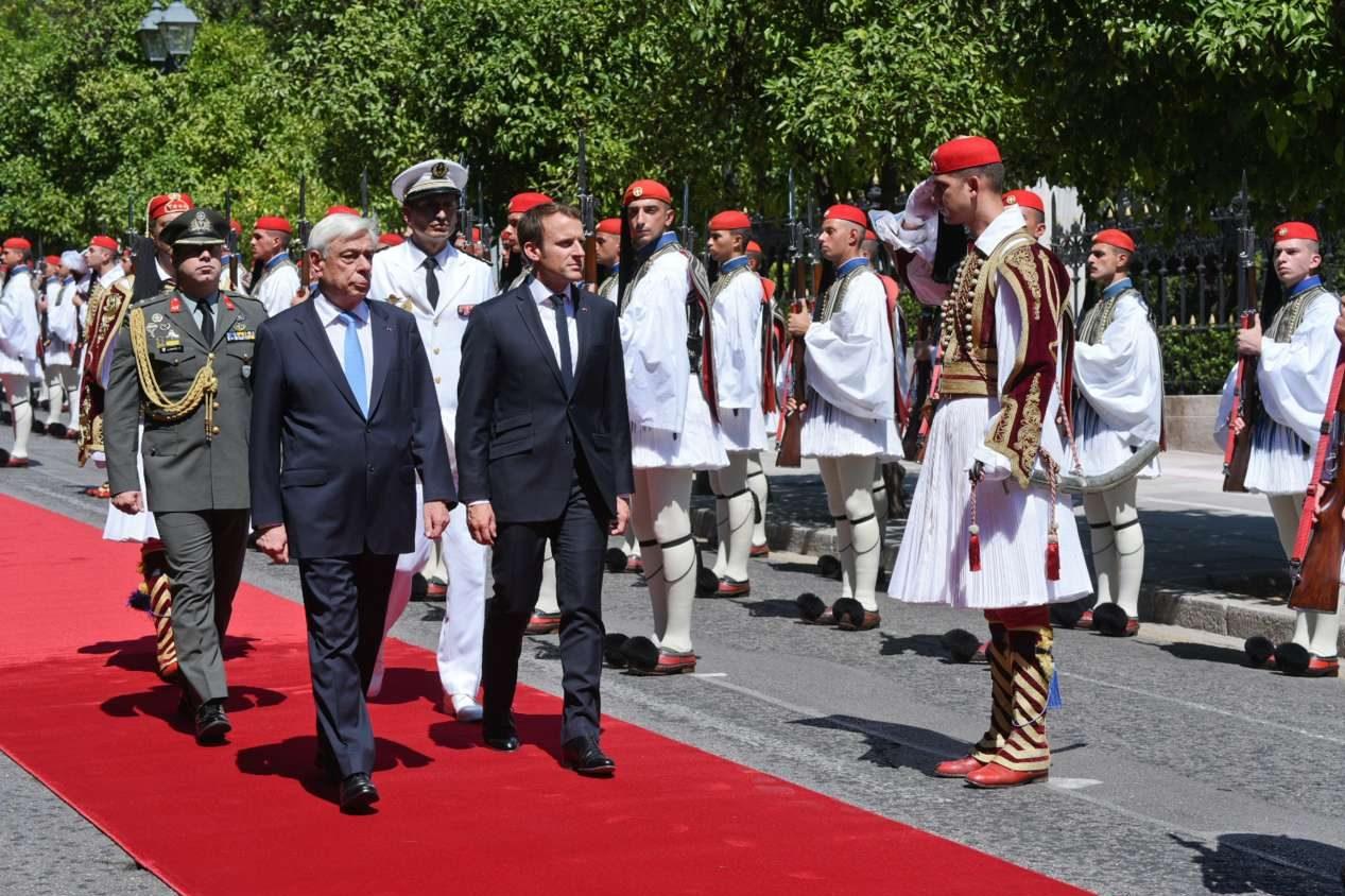 Προκόπης Παυλόπουλος και Εμανουέλ Μακρόν βαδίζουν στο κόκκινο χαλί στον δρόμο προς το Προεδρικό Μέγαρο