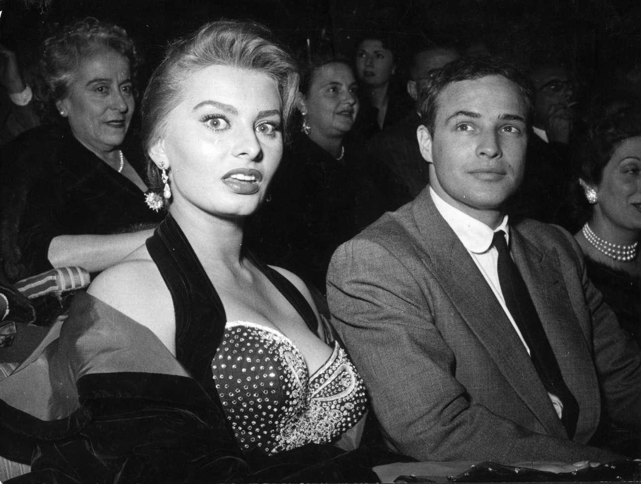 Νοέμβριος 1954, Ρώμη. Τα φλας των φωτογράφων αιφνιδιάζουν τη Σοφία Λόρεν που συνοδεύει τον Μάρλον Μπράντο σε βράβευσή του για το «Λιμάνι της Αγωνίας»