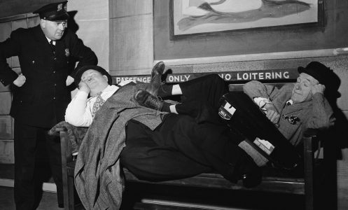 Comedy duo Stan Laurel (1890 - 1965) and Oliver Hardy (1892 - 1957) are found napping in front of a 'No Loitering' sign at a railway station in the sketch 'A Spot Of Trouble', performed on stage during their tour of the UK, 25th February 1952. The plot was a reworking of their 1930 comedy short 'Night Owls'. Actor Leslie Spurling plays the police officer.  (Photo by John Pratt/Keystone Features/Getty Images)