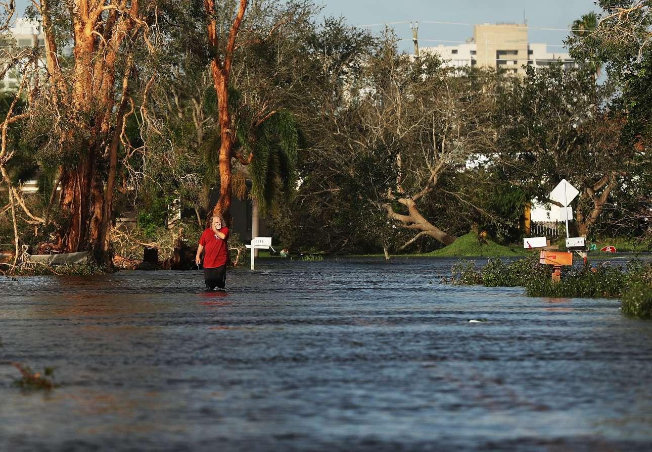 Στην πόλη Ναπλς της Φλόριντα, το νερό έφτανε μέχρι τα γόνατα του άνδρα που βαδίζει απεγνωσμένος στους πλημμυρισμένους δρόμους της γειτονιάς του