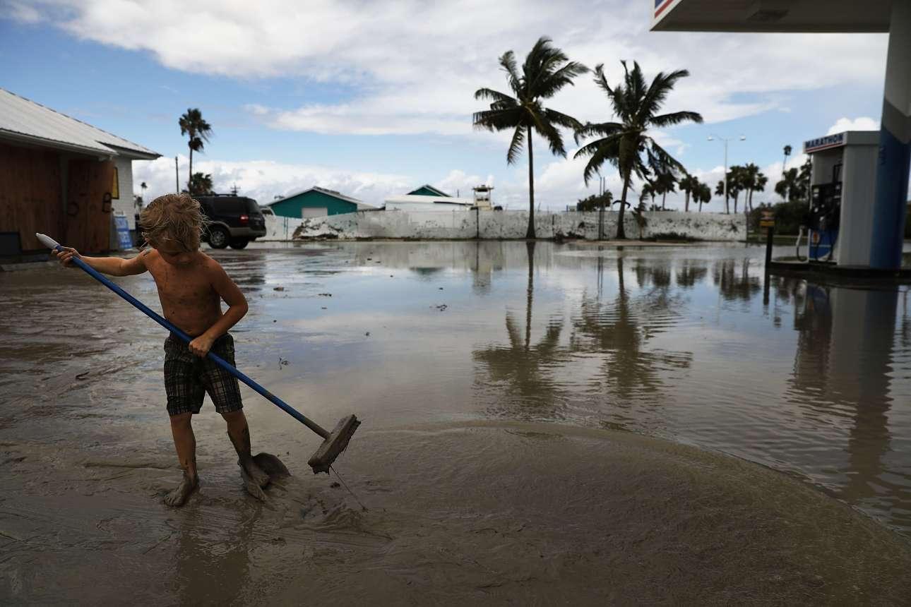 Πιτσιρικάς προσπαθεί να καθαρίσει το πλημμυρισμένο βενζινάδικο της οικογένειάς του στην περιοχή Έβεργκλεϊντς που μετρά τις πληγές της μετά το πέρασμα του τυφώνα