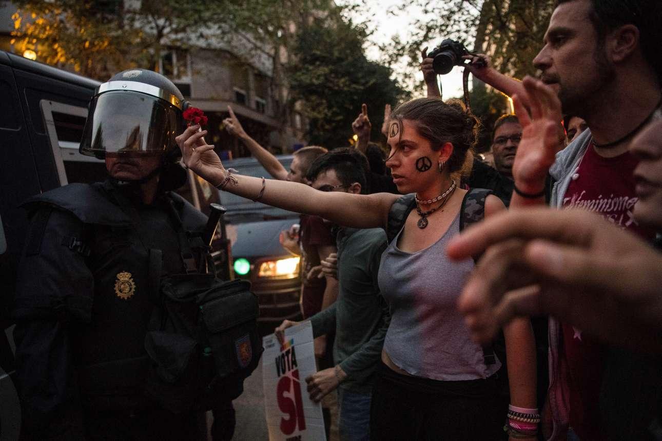 Τετάρτη, 20 Σεπτεμβρίου. Διαδηλωτές υπέρ της αυτονομίας της Καταλονίας απέναντι σε αστυνομικούς στην Βαρκελώνη. Μία νεαρή μάλιστα χαρίζει ένα κόκκινο γαρίφαλο στον πάνοπλο άνδρα της Αστυνομίας