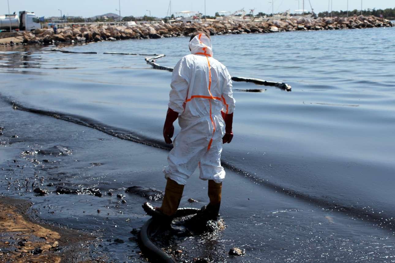 14 Σεπτεβρίου. Μέλος συνεργείου απορρύπανσης προσπαθεί να καθαρίσει παραλία της Γλυφάδας που έχει γεμίσει μαζούτ, λίγες μέρες μετά το ναυάγιο του «Αγία Ζώνη ΙΙ» στον Σαρωνικό, το οποίο προκάλεσε τεράστια οικολογική καταστροφή  στις θάλασσες της Αττική