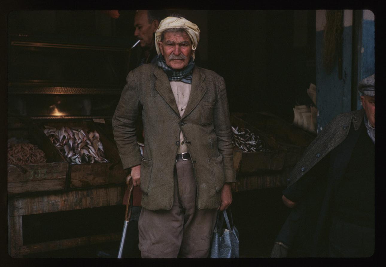 Εχοντας ψωνίσει φρέσκα ψάρια στο Ηράκλειο, ένας Κρητικός με βράκα και μαντήλι στο κεφάλι ποζάρει στον φακό του Κούσμαν