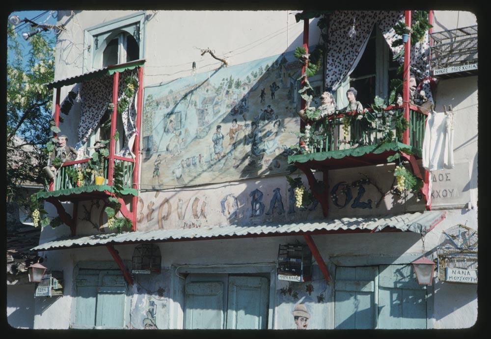 Η πολύχρωμη και παιχνιδιάρικη πρόσοψη μίας ταβέρνας στην οδό Βάκχου της Πλάκας, με διακοσμητικές κούκλες στα μπαλκόνια, τοιχογραφίες και ένα κλουβί πουλιού με ταμπέλα «Νανά Μούσχουρη»