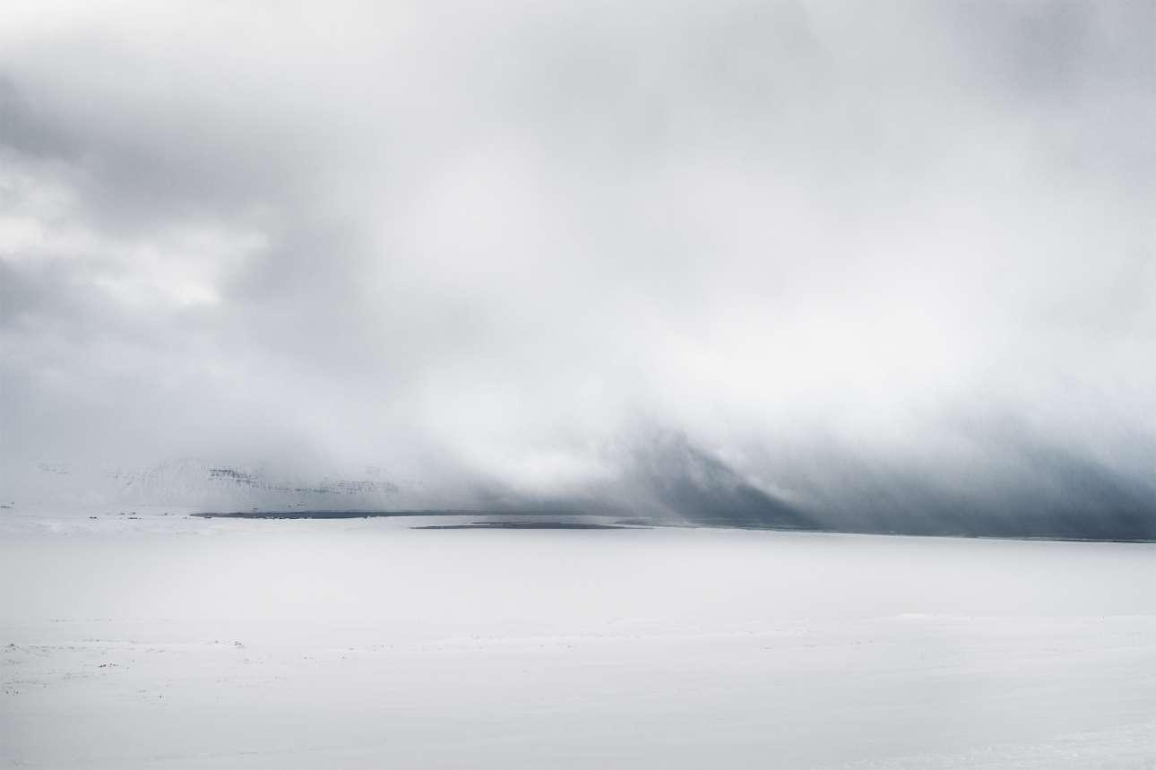 «Το Μάτι της Καταιγίδας». Πρώτη Θέση, κατηγορία «17 και άνω». Ταξιδεύοντας βόρεια από το Ρέικιαβικ στην Ισλανδία, ο φωτογράφος συνάντησε και απαθανάτισε το παραπάνω συγκλονιστικό τοπίο, όπου μέσα από τη βαριά χιονοθύελλα διακρίνεται ο ωκεανός