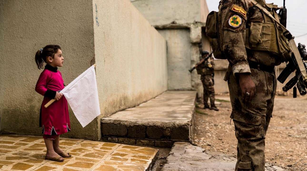 Με μια λευκή σημαία στα χέρια το κοριτσάκι από τη Μοσούλη στο Ιράκ υποδέχεται τους στρατιώτες που εκκαθαρίζουν τη συνοικία κατά τη διάρκεια της μάχης για την απομάκρυνση του ISIS