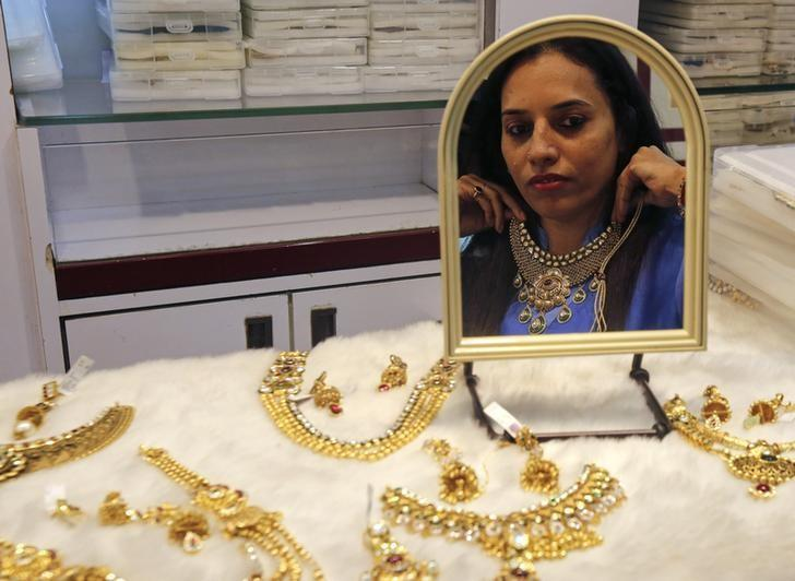 A woman tries on a gold necklace inside a jewellery showroom at a market in Mumbai January 15, 2015. REUTERS/Shailesh Andrade