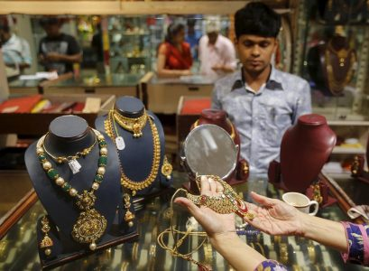 A customer tries a gold necklace at a jewellery showroom on the occasion of Dhanteras, a Hindu festival associated with Lakshmi, the goddess of wealth, at a market in Mumbai, November 9, 2015. REUTERS/Shailesh Andrade