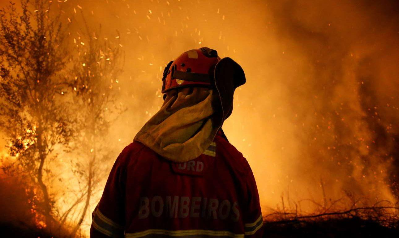 Τρίτη, 17 Οκτωβρίου, Λούσα. Ενας πυροσβέστης με φόντο το φλεγόμενο δάσος στο Καμπανόες, κοντά στην Λούσα της Πορτογαλίας