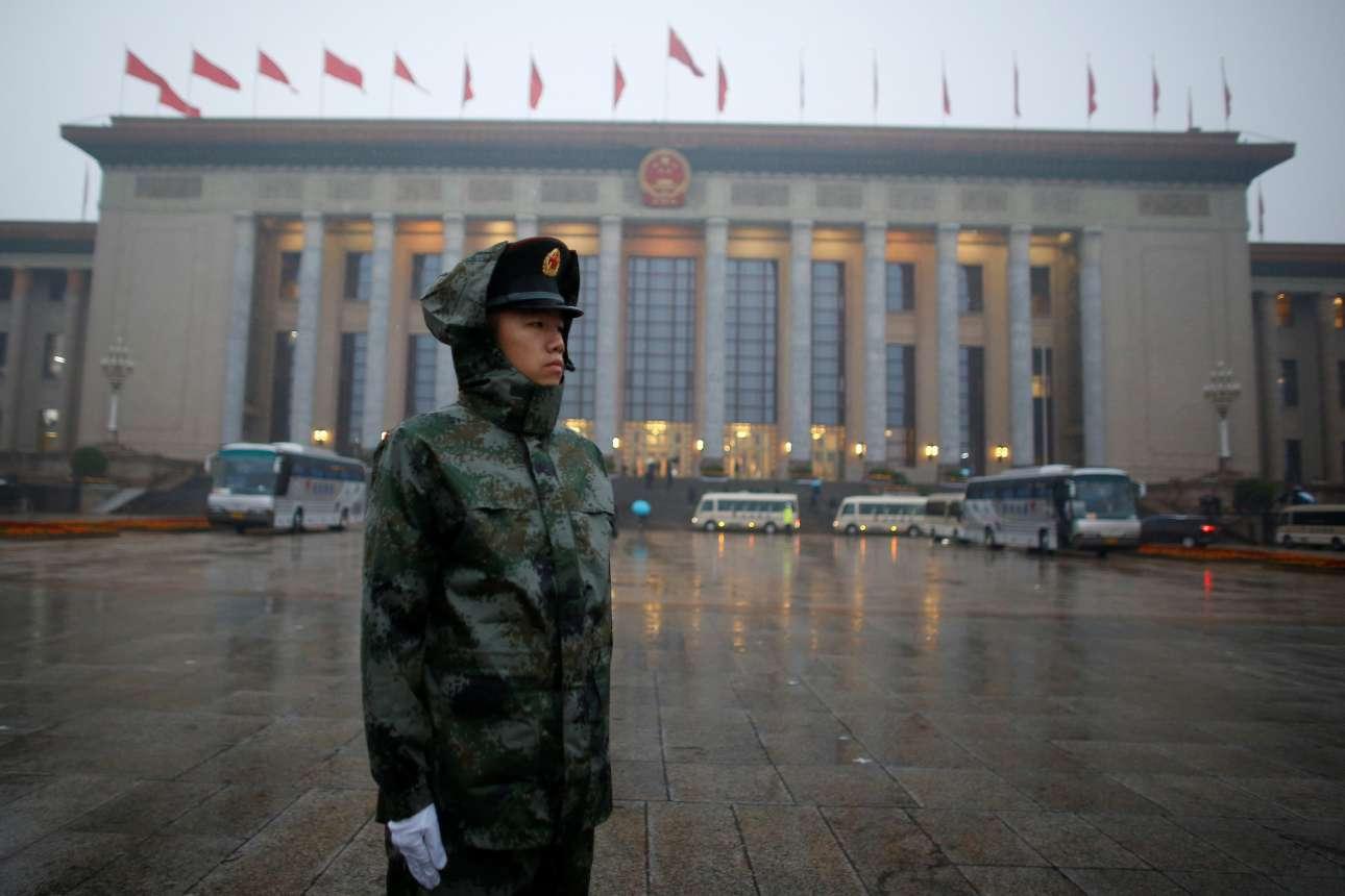 Αστυνομικός περιμένει μέσα στη βροχή έξω από τη μεγάλη αίθουσα του Συνεδρίου