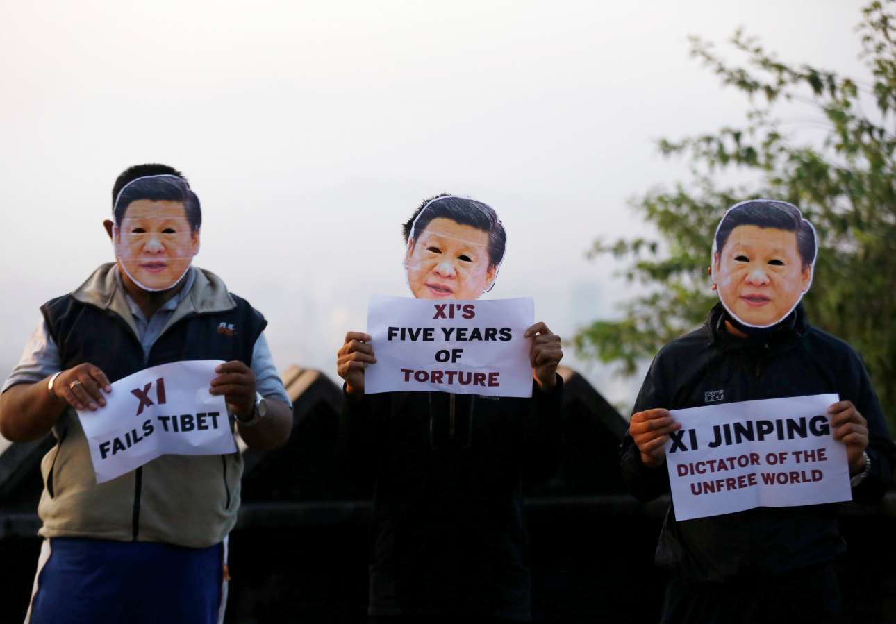 Μερικές χιλιάδες χιλιόμετρα από το Πεκίνο, στο Κατμαντού του Νεπάλ, θιβετιανοί ακτιβιστές με μάσκα Σι Τζινπίνγκ και συνθήματα εναντίον του