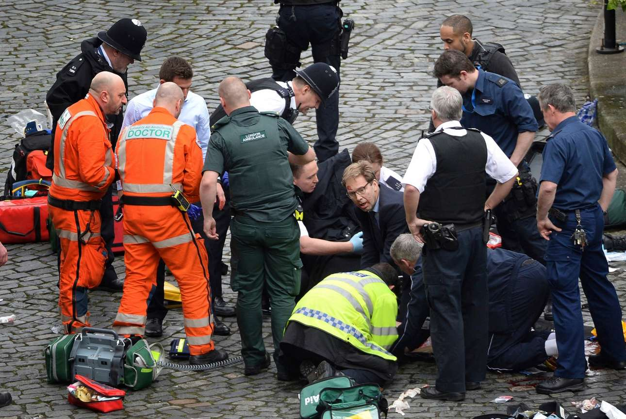 Αστυνομικοί, γιατροί και πολιτικοί σπεύδουν να βοηθήσουν τον αστυνομικό που ξεψυχάει έξω από το βρετανικό κοινοβούλιο, μετά το τρομοκρατικό χτύπημα που σημειώθηκε τον περασμένο Μάρτιο