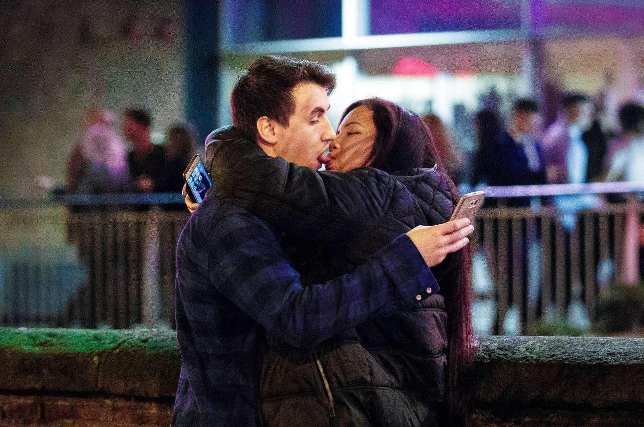 Ο έρωτας στα χρόνια της...τεχνολογίας. Ενα ζευγάρι φιλιέται -χωρίς να αφήσει τα κινητά από το χέρι- παραμονές Χριστουγέννων στο Μάντσεστερ, θυμίζοντας έντονα το γκράφιτι του Μπάνκσι «Mobile Lovers»
