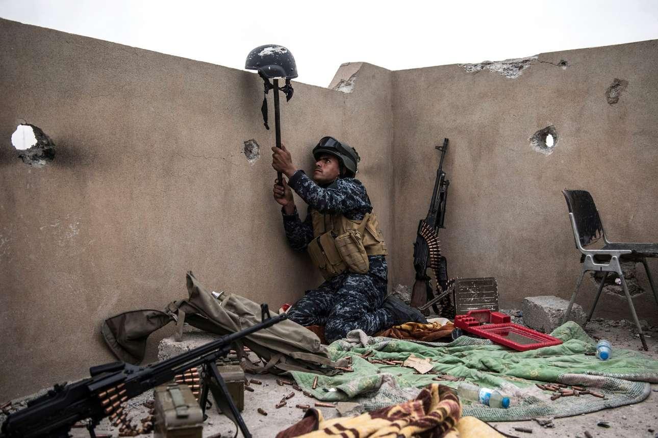 Ιρακινός κυβερνητικός στρατιώτης χρησιμοποιεί το κράνος του για να αποκαλύψει τη θέση σκοπευτή του Ισλαμικού Κράτους, σε μάχη για την ανακατάληψη της Μοσούλης