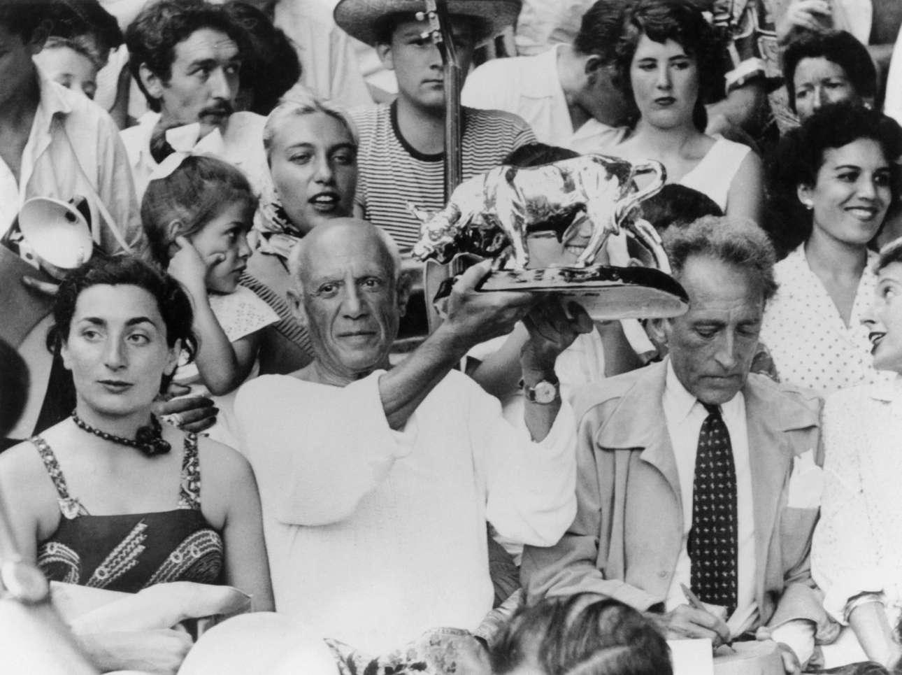 Στον ίδιο αγώνα ο Πικάσο λαμβάνει ένα δώρο από τους ταυρομάχους. Δίπλα του είναι η μετέπειτα σύζυγός του Ζακλίν Ροκ και ο Ζαν Κοκτό που κάτι σχεδιάζει