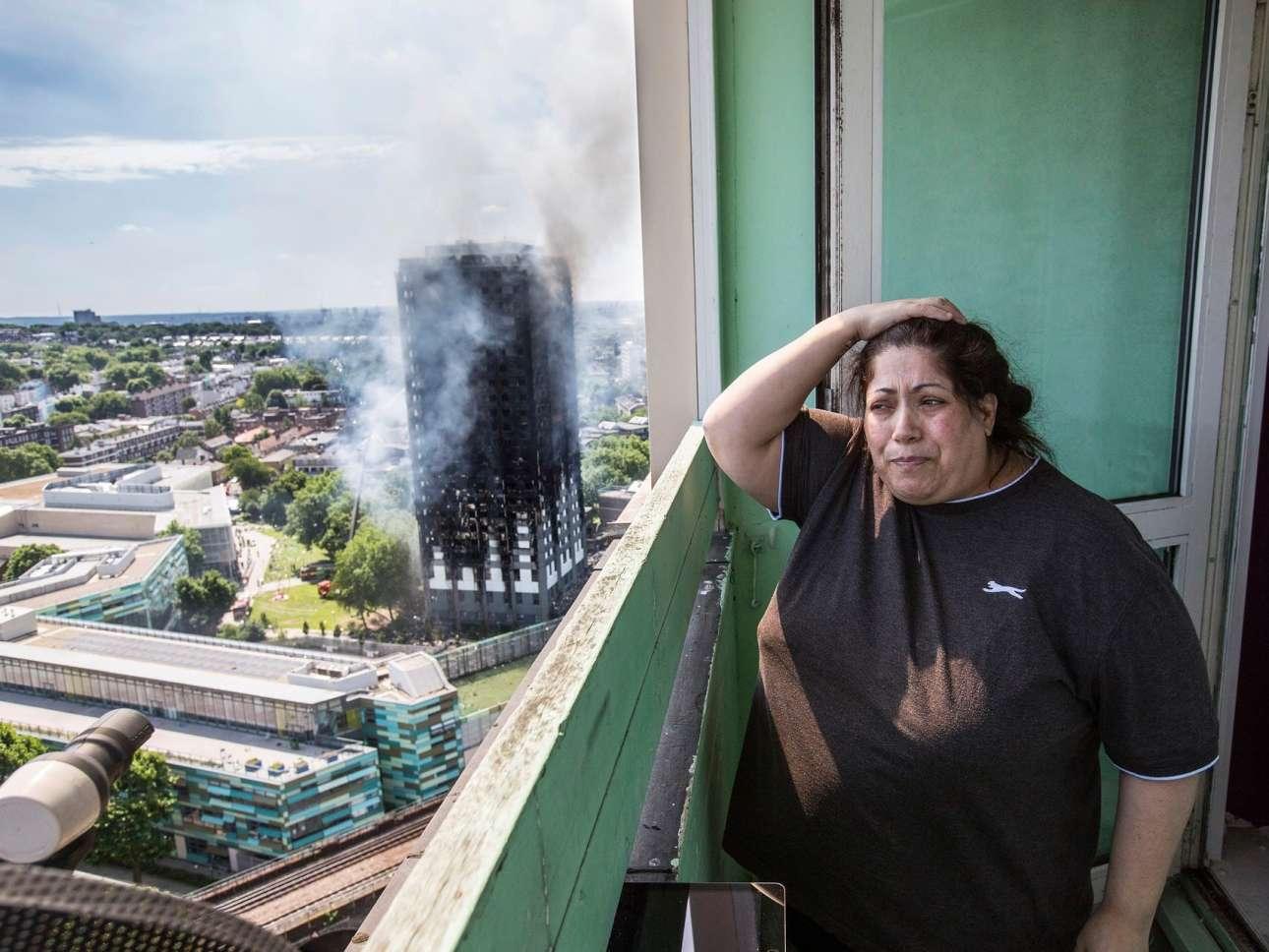 Πρώην ένοικος του Γκρένφελ, η Τζοτζίνα Αγκουίρε στέκεται απελπισμένη στο μπαλκόνι ενός κοντινού κτιρίου, με φόντο τον καρβουνιασμένο πύργο