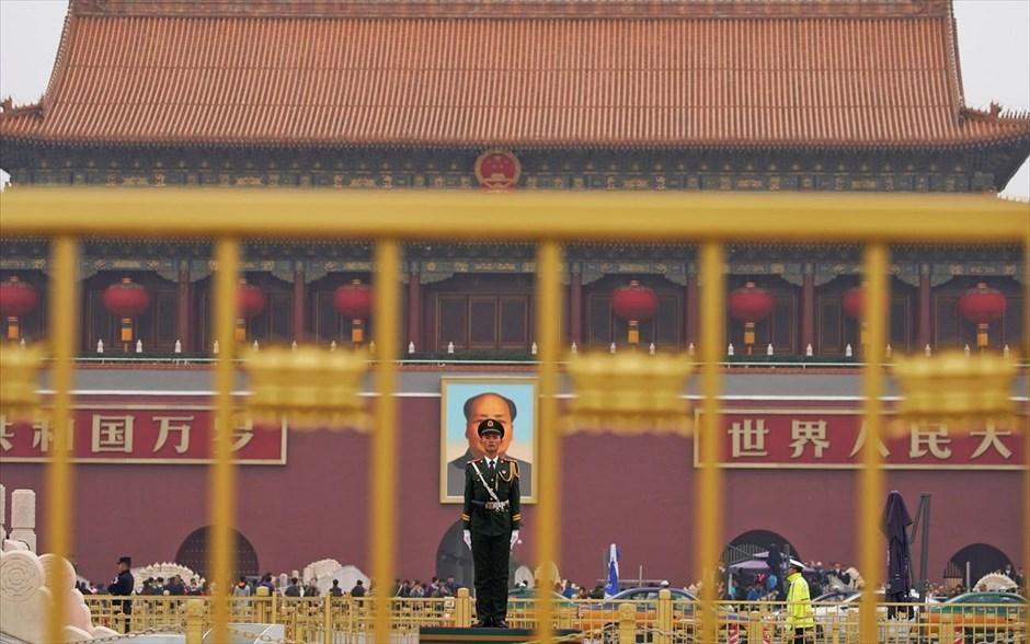 Τρίτη, 17 Οκτωβρίου, Πεκίνο. Φρουρός διακρίνεται μπροστά από το γιγαντιαίο πορτρέτο του ιδρυτή της Λαϊκής Δημοκρατίας της Κίνας, Μάο Τσε Τουνγκ που έχει στηθεί στην πύλη της Τιεν Αν Μεν, μία μέρα πριν από την έναρξη των εργασιών του 19ου Εθνικού Συνεδρίου του Κομμουνιστικού Κόμματος της Κίνας.