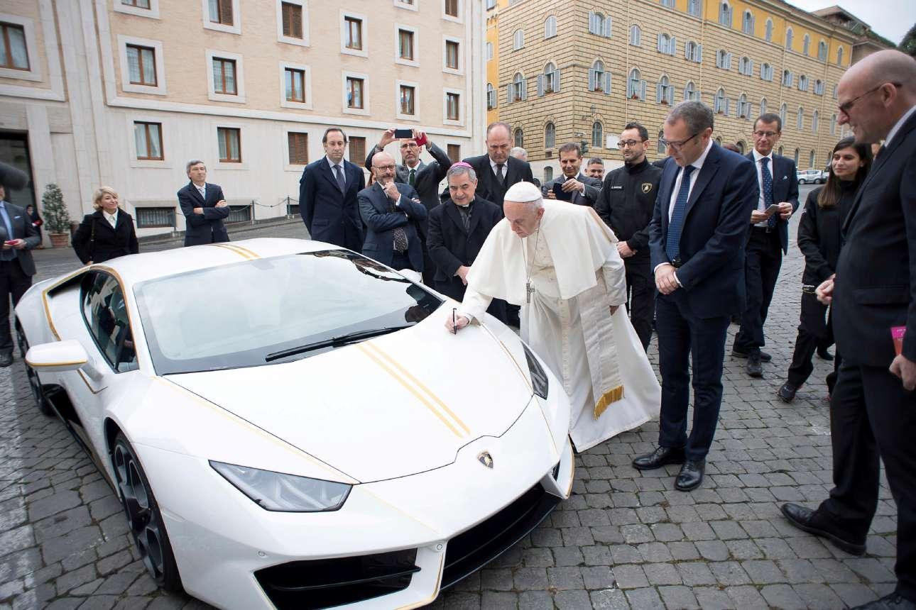Πέμπτη, 16 Νοεμβρίου, Βατικανό. Ο Πάπας Φραγκίσκος βάζει την υπογραφή του πάνω σε μία Lamborghini Huracan, μπροστά από την κατοικία του Σάντα Μάρτα, στο Βατικανό. Η ιταλική αυτοκινητοβιομηχανία Lamborghini παρουσίασε στον Πάπα τη νέα ειδική έκδοση της Huracan, η οποία θα δημοπρατηθεί και οι εισπράξεις θα διατεθούν για φιλανθρωπικούς σκοπούς
