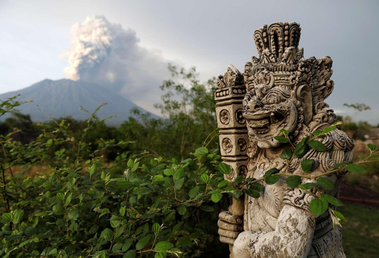 Ενα αρχαίο άγαλμα με φόντο το ενεργό ηφαίστειο