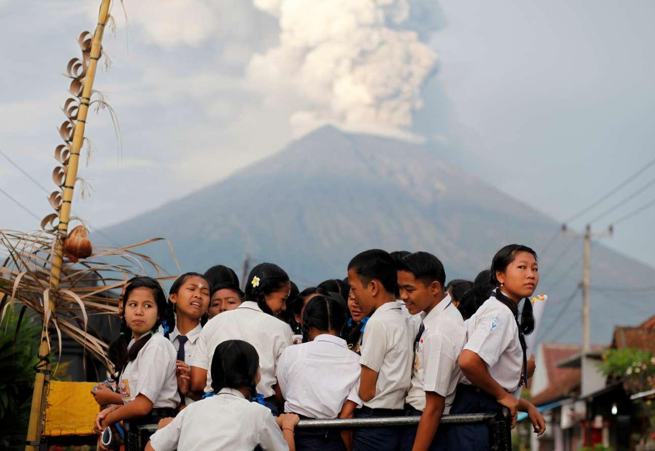 Μαθητές στον δρόμο για το σχολείο. Πίσω τους, το ηφαίστειο του όρους Αγκούνγκ βγάζει πυκνούς καπνούς