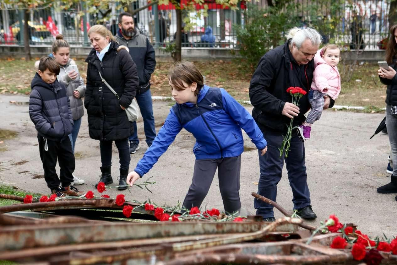 Μικροί και μεγάλοι αφήνουν λίγα κόκκινα τριαντάφυλλα πάνω στην πύλη που γκρέμισε το τανκ της χούντας