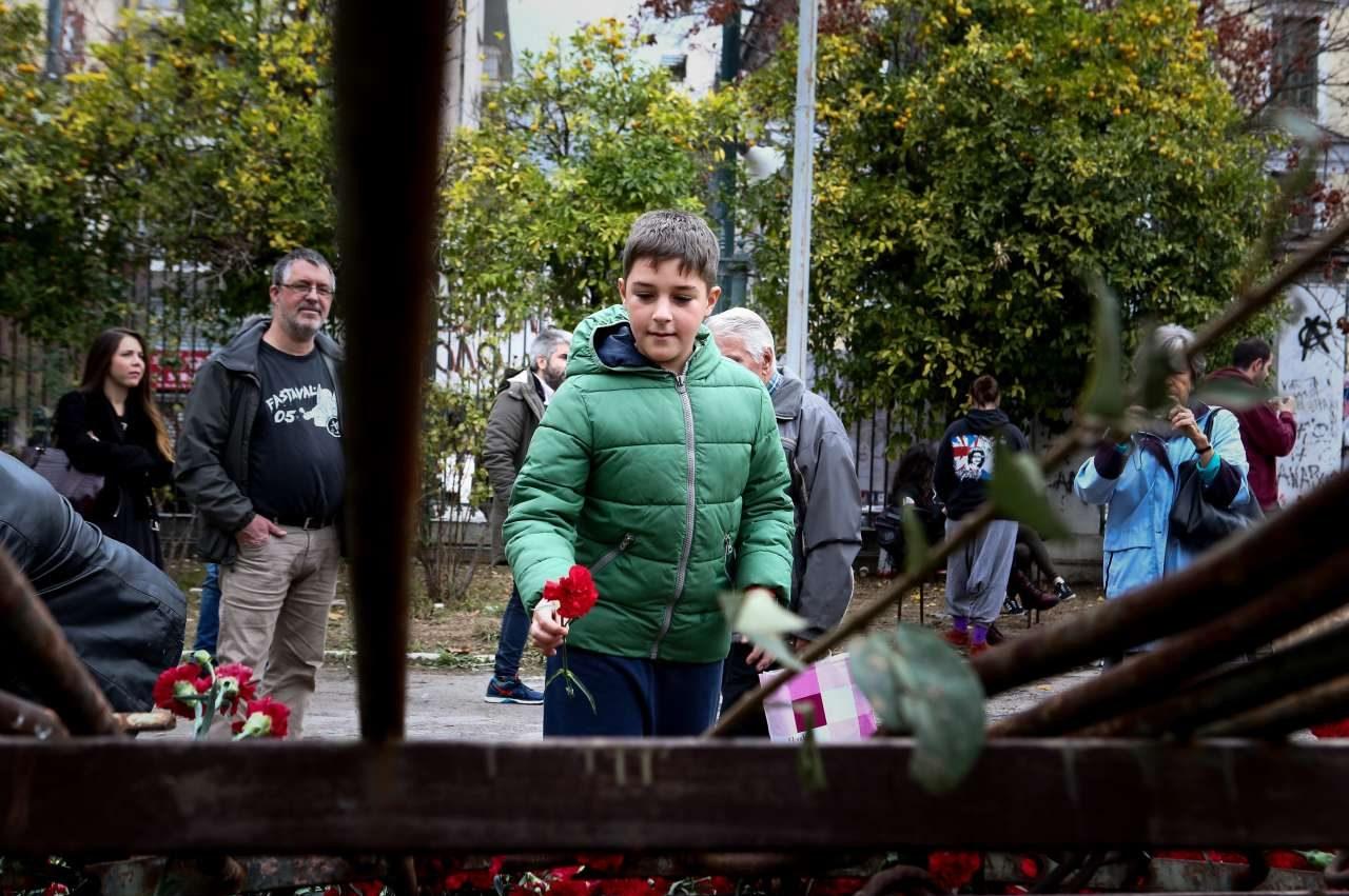 Ενας πιτσιρικάς αφήνει ένα κόκκινο λουλούδι