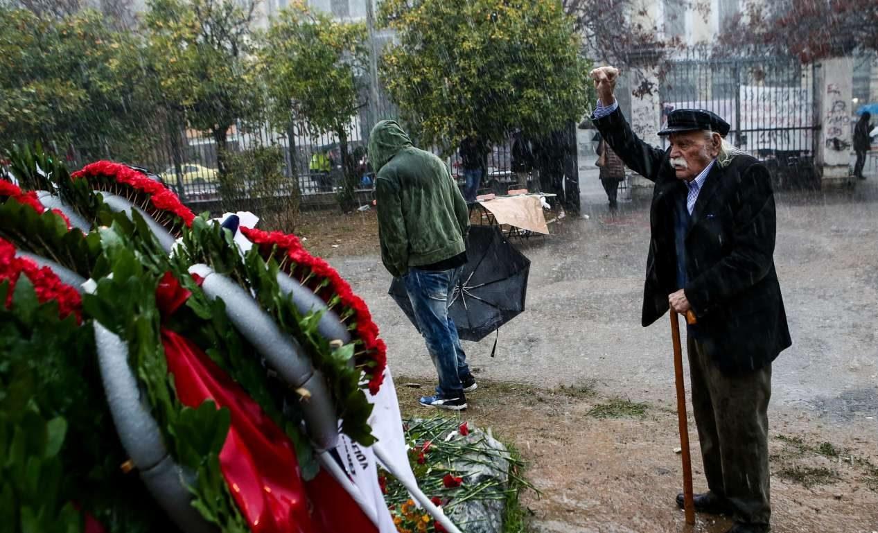 O Μανώλης Γλέζος στα 95 του, έχει αψηφήσει την καταρρακτώδη βροχή. Υψώνει τη γροθιά του μπροστά στο μνημείο των νεκρών αφού έχει αφήσει μερικά λουλούδια στο μνημείο