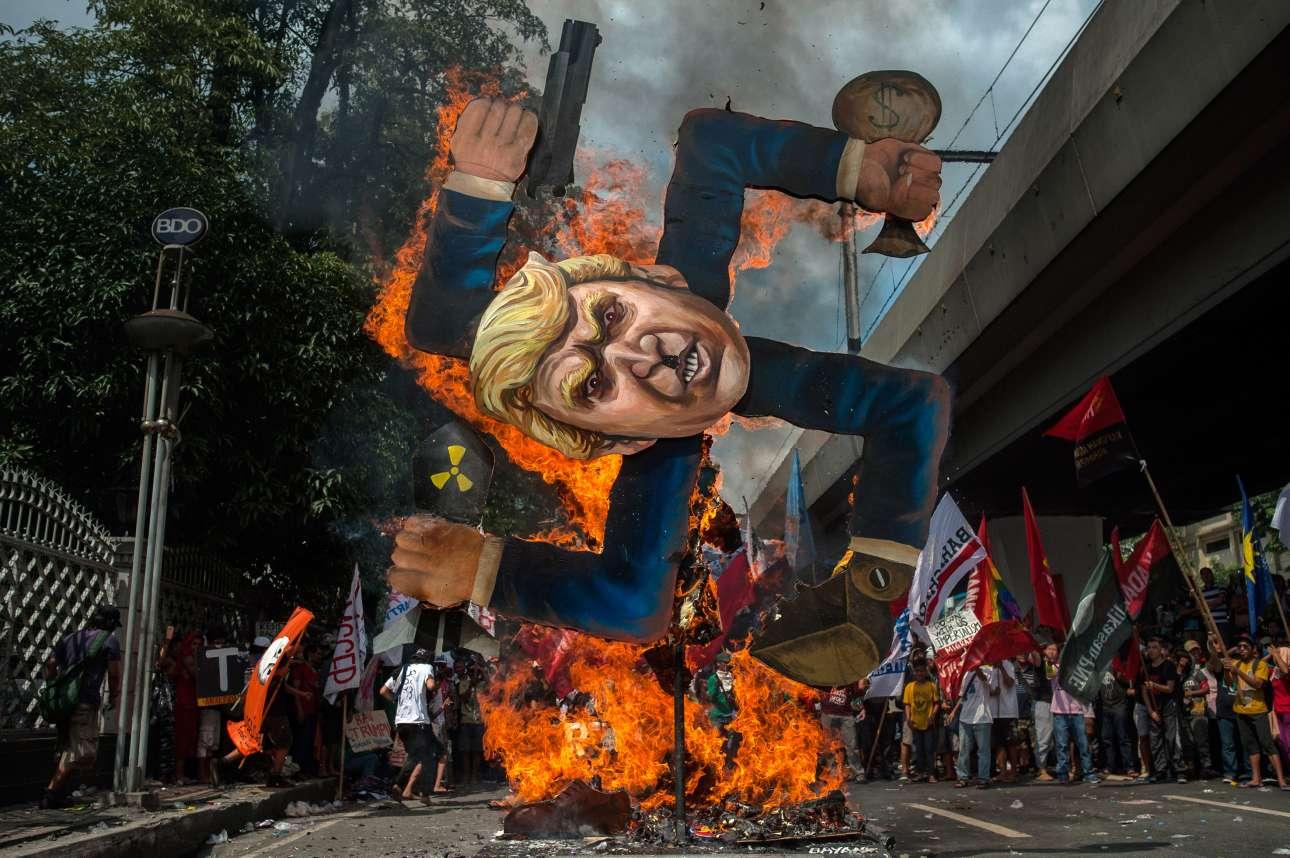Δευτέρα, 13 Νοεμβρίου, Μανίλα. Διαδηλωτές βάζουν φωτιά σε ένα ομοίωμα του Ντόναλντ Τραμπ σε σχήμα αγκυλωτού σταυρού στην πρωτεύουσα των Φιλιππίνων
