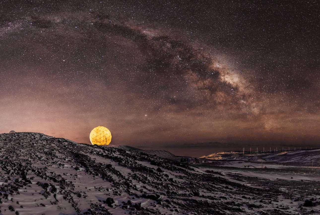 Ο εντυπωσιακός Γαλαξίας μας φωτίζει τον νυχτερινό ουρανό πάνω από τον σταθμό Μακμέρντο. Από κάτω βρίσκεται το δορυφορικό πιάτο της NASA Near Earth Network, γνωστό και ως «μπάλα του γκολφ» λόγω του σχήματος του, ένα από τα τρία δίκτυα διαστημικής επικοινωνίας των ΗΠΑ, το οποίο συλλέγει δεδομένα από δορυφόρους σε πολική τροχιά