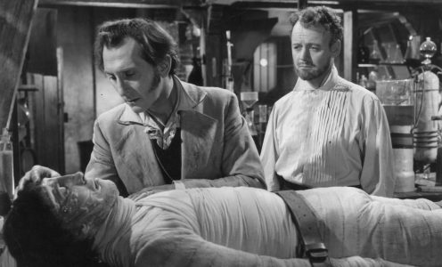 1957 Baron Frankenstein, played by Peter Cushing Christopher Lee, as Robert Urquhart  looks on. The scene is from 'The Curse of Frankenstein', di