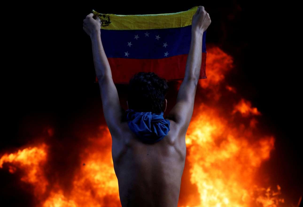 12 Ιουνίου. Διαδηλωτής σε πορεία κατά του καθεστώτος Μαδούρο κρατάει τη σημαία της Βενεζουέλας, με φόντο ένα κτίριο τυλιγμένο στις φλόγες