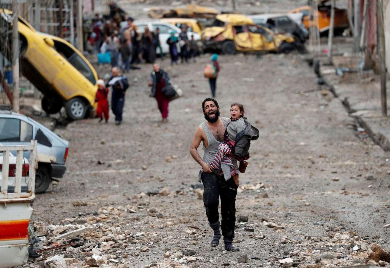 4 Μαρτίου. Μία συγκλονιστική εικόνα από το Ιράκ. Ενας πατέρας κλαίγοντας με την κόρη του αγκαλιά, τρέχει μακριά από το τμήμα της Μοσούλης που βρίσκεται υπό τον έλεγχο του Ισλαμικού Κράτους προς τους ιρακινούς στρατιώτες ειδικών δυνάμεων κατά τη διάρκεια μιας μάχης