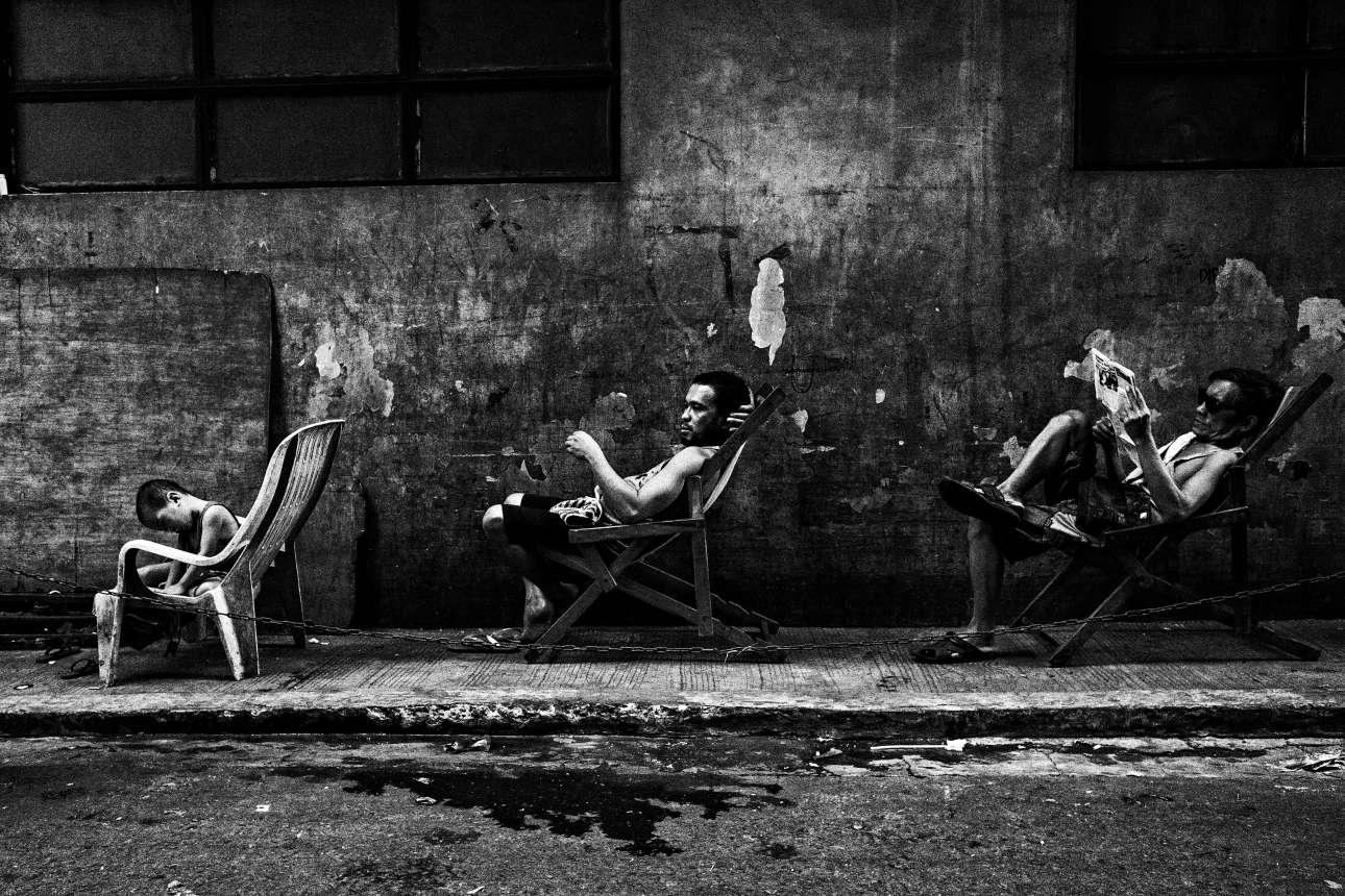 Τρεις γενιές ανδρών στη Μανίλα των Φιλιππίνων. Το παιδί παίζει, ο μεσήλικας φαίνεται να σκέφτεται κάτι σοβαρό και στο τέλος ο ηλικιωμένος διαβάζει χαλαρός την εφημερίδα του. «Είναι σαν την εξέλιξη από το να είσαι ένα παιχνιδιάρικο παιδί σε ένα χαλαρό, χωρίς ανησυχίες, γέρο άνδρα» λέει ο φωτογράφος