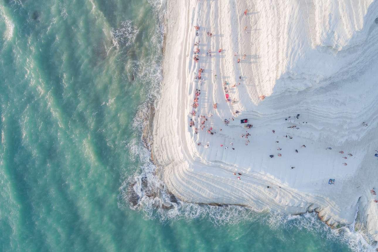 «Η μεγάλη μαρέγκα». Η δημοφιλής παραλία «Τούρκικα σκαλοπάτια» στη Σικελία, φωτογραφημένη από ψηλά. Το όνομα της παραλίας με τα λεπτά, ανάγλυφα λευκά βράχια από ασβεστόλιθο που θυμίζουν μαρέγκα, βγήκε από τις συχνές επιδρομές που έκαναν παλιότερα οι τούρκοι πειρατές στην περιοχή