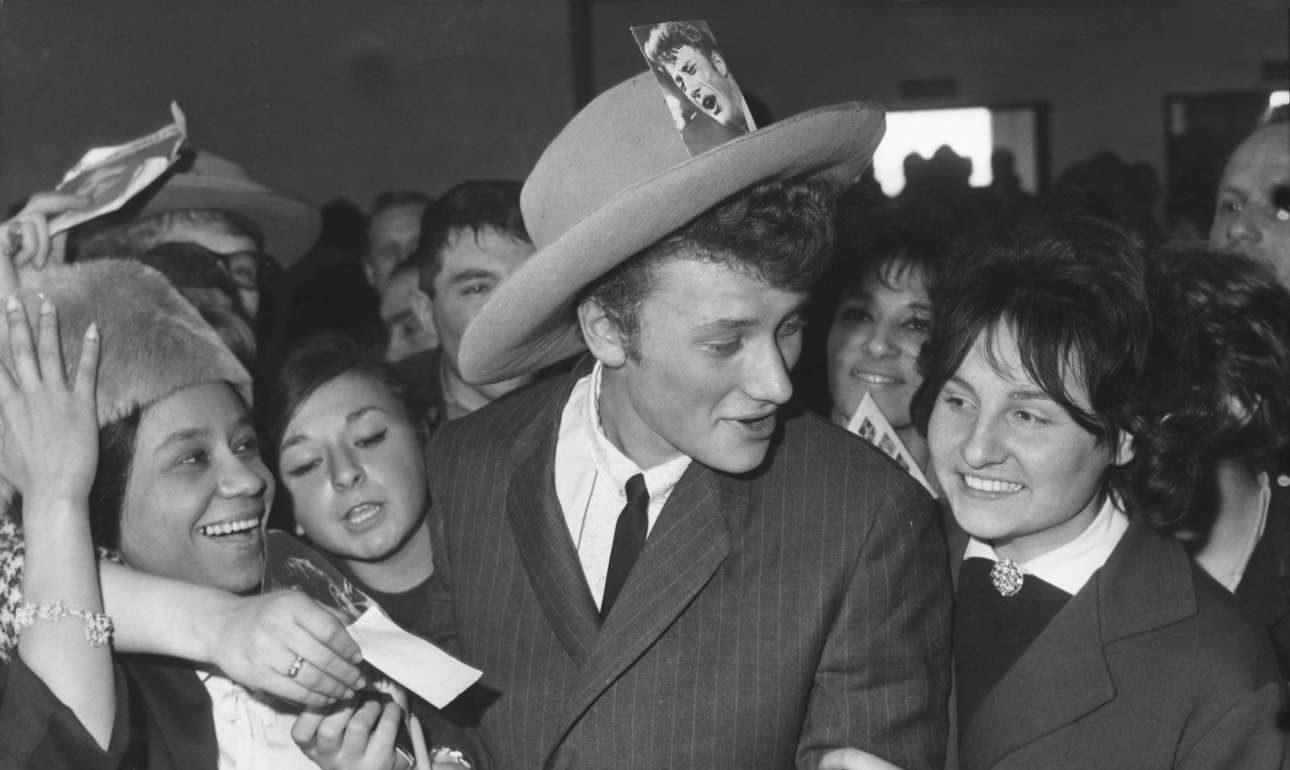 Ο Χολιντέι επιστρέφει στο Παρίσι από περιοδεία στις ΗΠΑ το 1962. Είχε τολμήσει να κάνει το υπερατλαντικό τραγούδι πριν από τους Beatles
