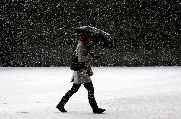 Γυναίκα προσπαθεί να περπατήσει επάνω σε στρώμα χιονιού και πάγου (REUTERS/Francois Lenoir)