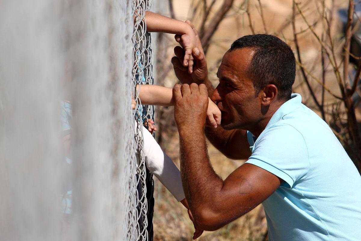 10 Σεπτεμβρίου.  Ο Αμάρ Χαμάσο από τη Συρία, ο οποίος ζει στην Κύπρο, πέφτει στα γόνατα και φιλά τα χέρια των παιδιών του πίσω από την περίφραξη του καταυλισμού της Κοκκινοτριμιθιάς έξω από την Λευκωσία. Ο Αμάρ είχε χωριστεί από τη γυναίκα του και τα τέσσερα παιδιά του πριν από ένα χρόνο, μετά από αεροπορική επιδρομή  στην πόλη Ιντλίμπ της Συρίας