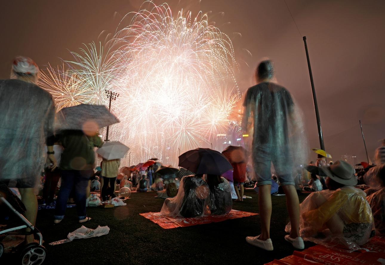 Υπό καταρρακτώδη βροχή, αμέτρητοι πολίτες στη Σιγκαπούρη έσπευσαν στο λιμάνι για να θαυμάσουν τα πυροτεχνήματα